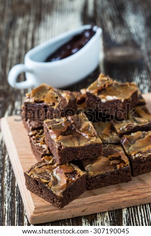 Homemade caramel chocolate brownies on wooden board - stock photo