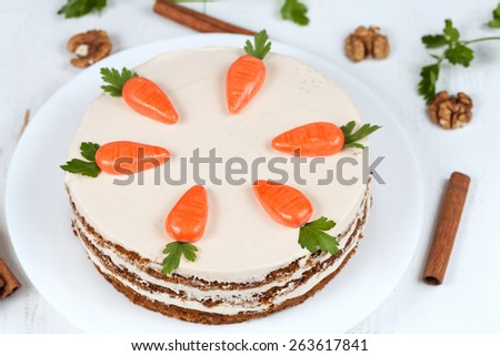 Homemade carrot cake with little carrots on top on white background - stock photo