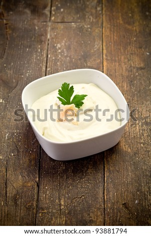 homemade cheese sauce with parsley leaf on wooden table