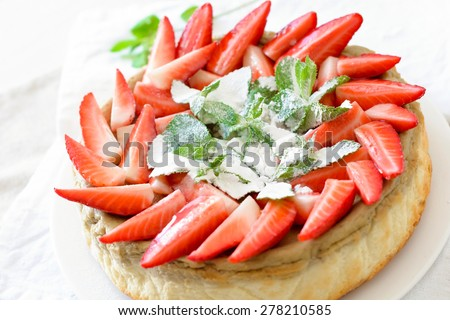 Homemade cheesecake decorated with fresh strawberries, mint and powdered sugar, close up selective focus - stock photo