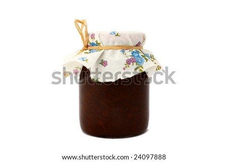 Homemade cherry jam in a jar covered with color linen diaper.