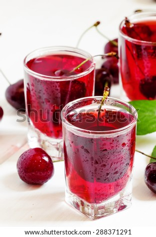 Homemade cherry liqueur and fresh cherries on white wooden background, selective focus