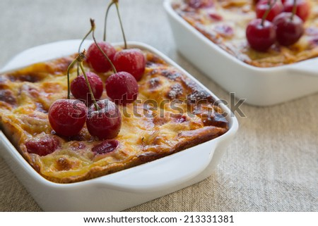 Homemade cherry mini pies in the ceramic baking mold on the linen cloth.Close up - stock photo