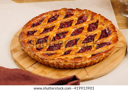 Homemade cherry pie on rustic background with cup of tea