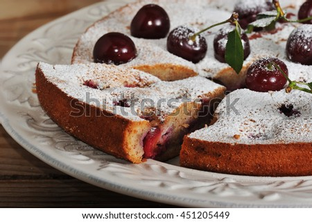 Homemade cherry pie on rustic background with whole cherries