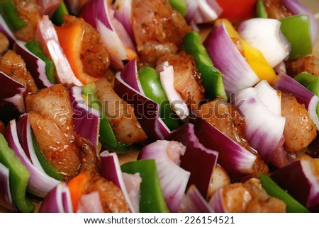 Homemade chicken an bacon skewers kebabs with peppers, onions and herbs marinade on wooden bamboo background - stock photo