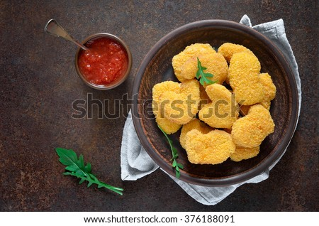 Homemade chicken breast nuggets served with tomato sauce - stock photo