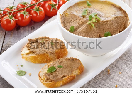 Homemade chicken liver pate on  baguette adn in white bowl with tomatoes - stock photo