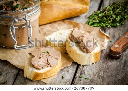 homemade chicken liver pate with fresh baguette and thyme on rustic wooden table - stock photo