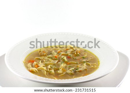 Homemade chicken noodle soup on a white background. - stock photo