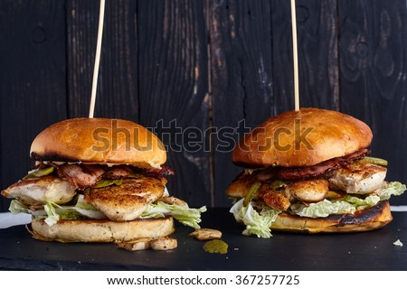 Homemade chicken sandwich (burger) with mushrooms, chinnese cabbage, pickles and ketchup in burger bun on dark wood background - stock photo