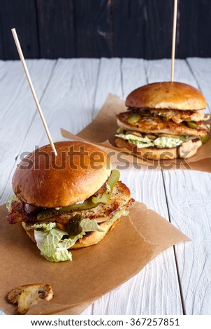 Homemade chicken sandwich or burger with mushrooms, chinnese cabbage, pickles, chicken breast and ketchup in homemade burger bun on wood background - stock photo