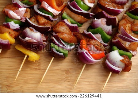 Homemade chicken skewers kebabs with peppers, onions, beacon and herbs marinate on wooden bamboo background - stock photo