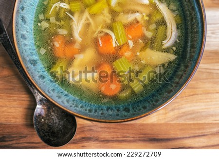 Homemade chicken soup in a turquoise bowl with an antique soup spoon on a wooden table.  - stock photo