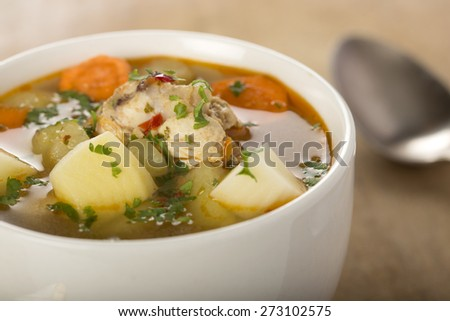 Homemade chicken soup in a white bowl with an antique soup spoon on a wooden table - stock photo