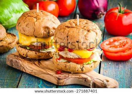 homemade chikenburgers with fresh vegetables on rustic wooden table - stock photo