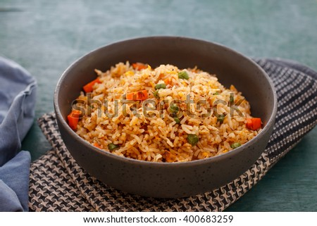 Homemade Chinese fried rice with vegetables, fried eggs served on a small pan, image dark tone and soft focus. - stock photo