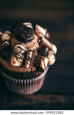Homemade chocolate and crunchy cupcake on wooden background, selective focus