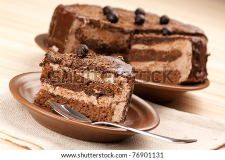 Homemade chocolate cake and spoon on beige mat. - stock photo