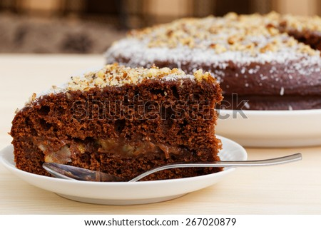 Homemade chocolate cake with walnut and peach on the wooden table - stock photo