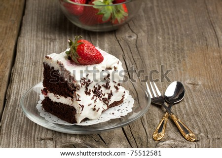 Homemade chocolate cake with whipped cream and fresh strawberry on old wooden table - stock photo