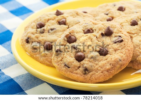 Homemade, chocolate chip cookies, like Mom used to make, served on a yellow plate.  Shallow depth of field. - stock photo