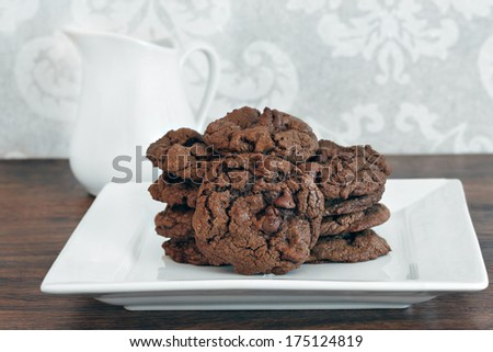 Homemade chocolate chocolate chip cookies stacked on a white plate.  Closeup front view. - stock photo