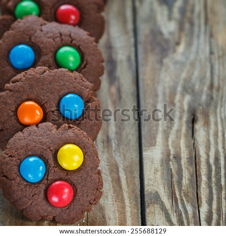 Homemade  chocolate cookies decorated with colorful candy drops, square - stock photo