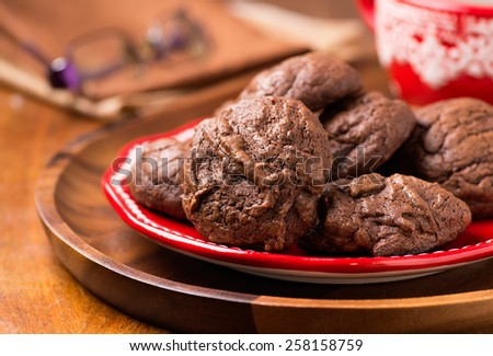Homemade chocolate cookies on red plate, selective focus - stock photo