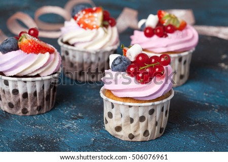 Homemade chocolate cupcakes with pink cream cap and berries on a dark Homemade vanilla and chocolate cupcakes with pink cream cap and berries on a dark blue background.blue background.