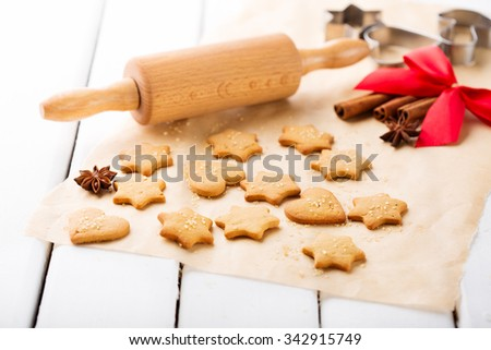 Homemade Christmas gingerbread cookies with festive decoration on white wooden background, selective focus