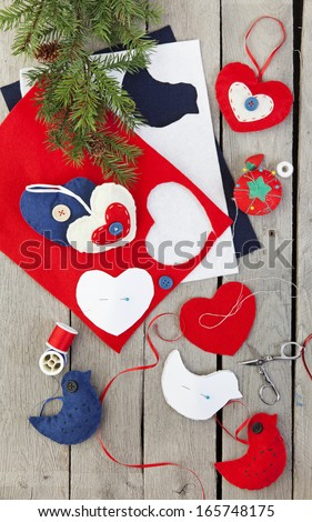 Homemade Christmas ornaments being made from felt, ribbon, and buttons. - stock photo