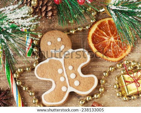 Homemade christmas painted gingerbreads (gingerbread man and red present) on the wooden background with Christmas decorations, cones and candied orange. Selective focus on the man. Toned and snow - stock photo