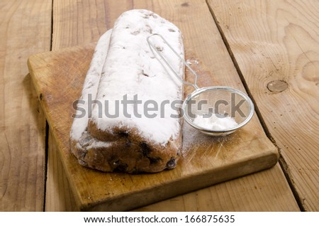 homemade christmas stollen with powdered sugar on a wooden board