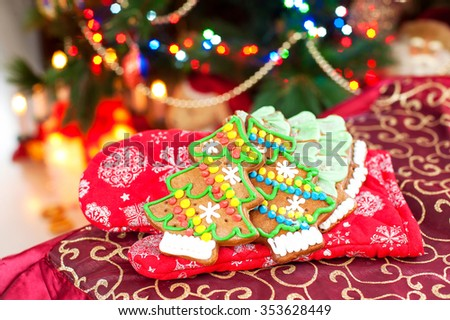 Homemade christmas tree shape gingerbread cookies on oven mitten. Illuminated festive background. Multicolored horizontal indoors image.