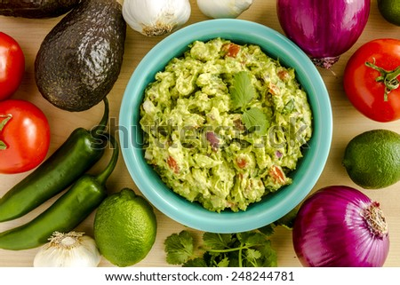 Homemade chunky guacamole in bright blue bowl garnished with cilantro surrounded by dip ingredients - stock photo