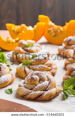 Homemade cinnamon buns with pumpkin on paper over brown background
