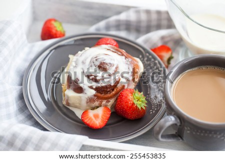 Homemade cinnamon roll pastry with icing and strawberry - stock photo