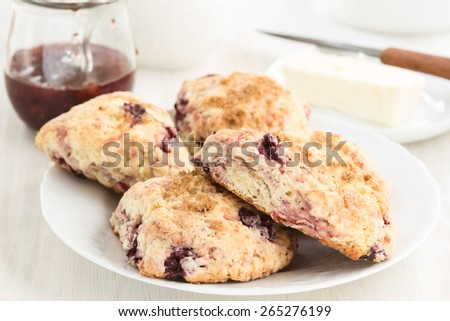 Homemade classic bakery, cream scones with cherry.  Traditional Irish  quick bread served with butter and preserves - stock photo
