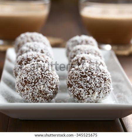 Homemade coconut rum balls on plate, glass cups of hot chocolate in ...