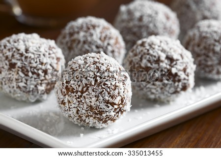 Homemade coconut rum balls on plate, photographed with natural light (Selective Focus, Focus on the first ball) - stock photo