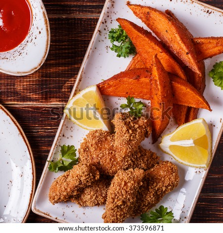 Homemade cooked nuggets, sweet potatoes and coleslaw on dark wooden background. - stock photo
