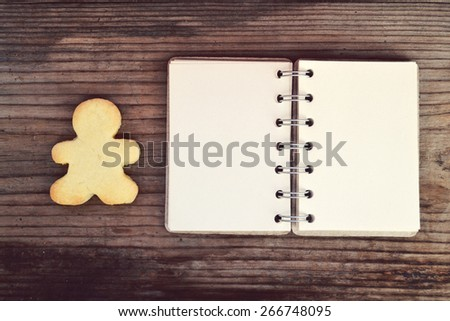 Homemade cookie in shape of man and empty retro spiral recipe book on wooden table - stock photo