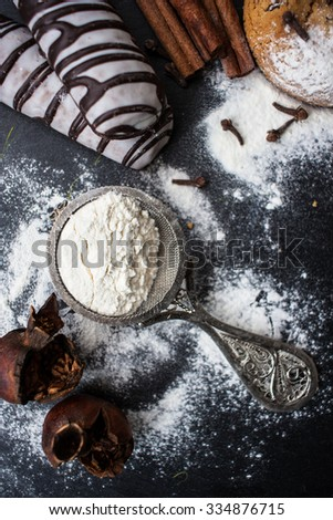 homemade cookies and various ingredients on a kitchen table - stock photo