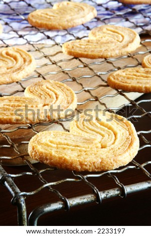 Homemade cookies on a baking tray.  Very shallow D.O.F - foreground in focus, background out of focus. - stock photo