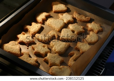 homemade cookies, stars and hearts on a baking tray fresh out of the oven - stock photo