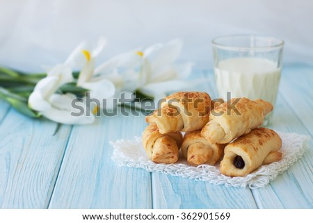 Homemade cookies, sweet rolls with raisins, mini croissants, with white iris flowers and glass of milk on rustic wooden board. Breakfast on Valentine's Day. Selective focus - stock photo