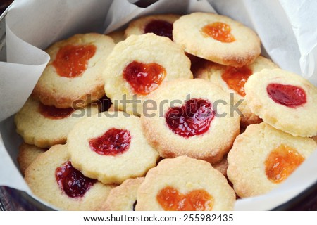 Homemade cookies with heart shaped jam on wooden table - stock photo