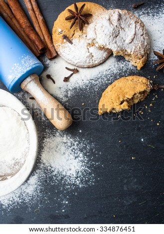 Homemade cookies with ingredients and utensils on a dark kitchen background - stock photo
