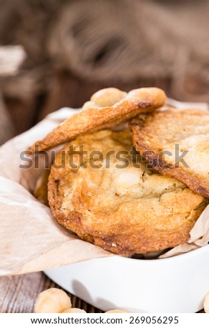 Homemade Cookies with Macadamia nuts and white chocolate (on wooden background) - stock photo